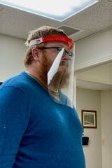 Michael Hunter tries on the face shield prototype he built at APSU's GIS Center.