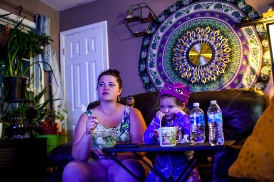 Teala Goff, left, and her daughter Raegyn Goff, right, watch a television show with their conure Adi perched on Teala's shoulder at the Goff household in Oak Grove, KY., on Tuesday, April 14, 2020.