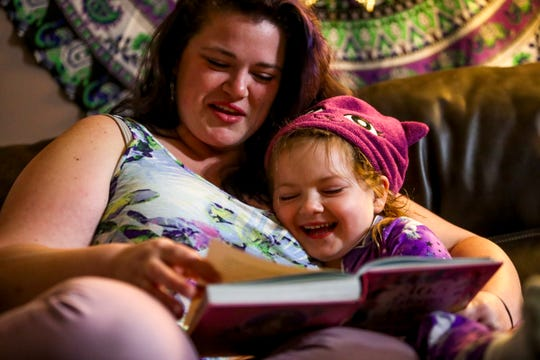 Teala Goff reads a story to her daughter Raegyn after a long day and before the two retire to bed at the Goff household in Oak Grove, KY., on Tuesday, April 14, 2020.