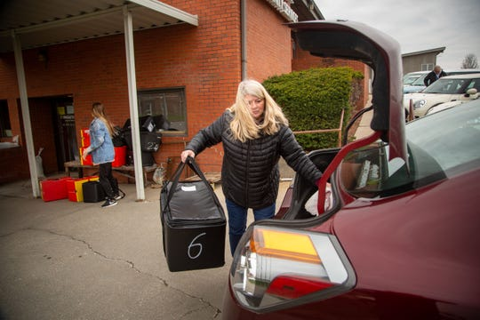 Volunteers Gayla Baughman and her daughter Maggie unload their car after making deliveries for WesleyLifeÕs Meals on Wheels program Thursday, April 16, 2020.