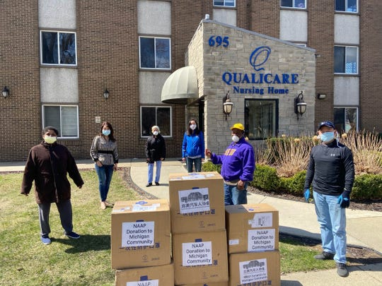 Terry Ellsberry (far left), a certified nursing assistant and SEIU steward at Qualicare Nursing Home in Detroit; State Sen. Stephanie Chang, D-Detroit (fourth from left), and Joe Miao (far right) with the boxes of 12,000 donated face masks from the North American Auto Professional Association.