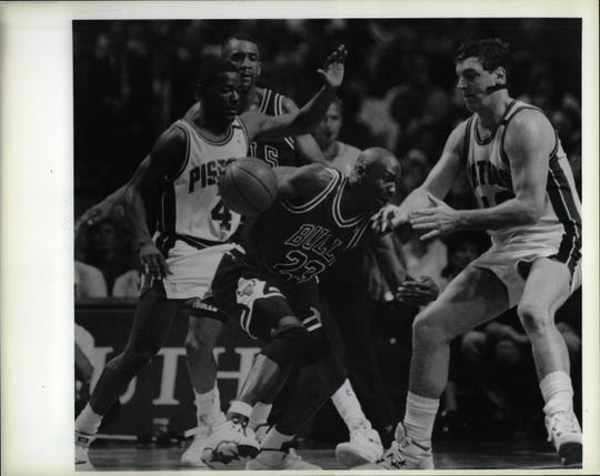 Pistons' Joe Dumars, left, and Bill Laimbeer apply the