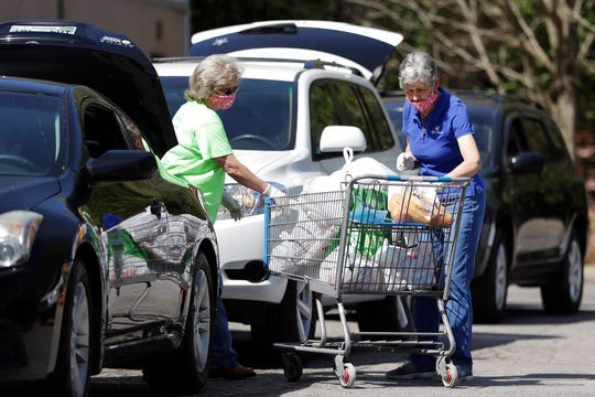 In this April 9, 2020, photo, workers Nellie King, left, and Sylvia Ware, right, load food and supplies into a family's trunk at GraceWorks Ministries food pantry in Franklin, Tenn.
