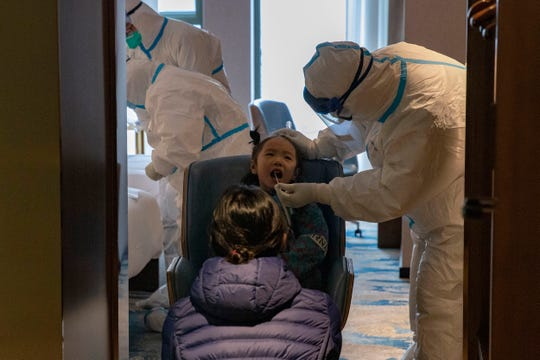 In this March 31, 2020, photo, a child takes a COVID-19 test at a quarantine hotel in Wuhan in central China's Hubei province. Top Chinese officials secretly determined they were likely facing a pandemic from a novel coronavirus in mid-January, ordering preparations even as they downplayed it in public.