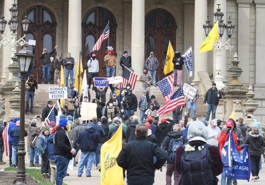"""Prostesters, from their cars and on foot, surround the State Capitol during """"Operation Gridlock"""" in Lansing, Michigan on April 15, 2020."""