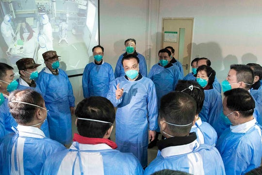 In this Jan. 27, 2020, photo released by China's Xinhua News Agency, Chinese Premier Li Keqiang, center, speaks with medical workers at Wuhan Jinyintan Hospital in Wuhan. Top Chinese officials secretly determined they were likely facing a pandemic from a novel coronavirus in mid-January, ordering preparations even as they downplayed it in public. Internal documents obtained by the AP show that because warnings were muffled inside China, it took a confirmed case in Thailand to jolt Beijing into recognizing the possible pandemic before them.