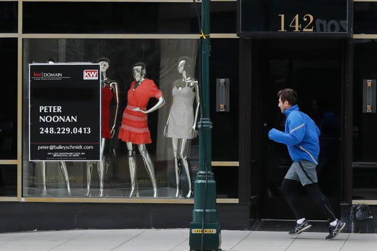 A jogger runs past Rococo, a clothing store, Thursday, April 16, 2020, in Birmingham, Mich. The government's lending program for small businesses is on hold. The Small Business Administration said Thursday that it reached the $349 billion lending limit for the program, after approving nearly 1.7 million loans.