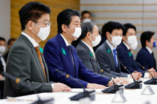 Japanese Prime Minister Shinzo Abe, center, wearing a face mask, speaks, during the country's coronavirus task force meeting at his official residence in Tokyo Thursday, April 16, 2020.  Prime Minister Abe has expanded an ongoing state of emergency to all of Japan from just Tokyo and other urban areas as the virus continued to spread.