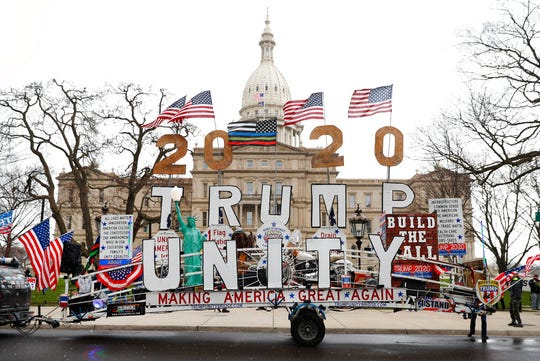 A Trump Unity sign on a trailer is shown parked at a protest in front of the Michigan State Capitol in Lansing, Mich., Wednesday, April 15, 2020. Flag-waving, honking protesters drove past the Michigan Capitol on Wednesday to show their displeasure with Gov. Gretchen Whitmer's orders to keep people at home and businesses locked during the new coronavirus COVID-19 outbreak.