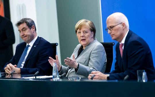 Markus Soder, Prime Minister of Bavaria, left, Germany's Chancellor Angela Merkel, center, and Peter Tschentscher, First Mayor of Hamburg, speak at a press conference in the Federal Chancellery, Berlin, Wednesday April 15, 2020.