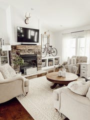 Open to the kitchen and the foyer, the living room is dressed in the same creamy whites and neutrals and punctuated with antiques. New upholstered furniture is from Wayfair.
