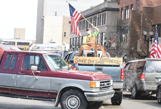 """Protesters, from their cars and on foot, surround the State Capitol during """"Operation Gridlock"""" in Lansing, Michigan on April 15, 2020."""