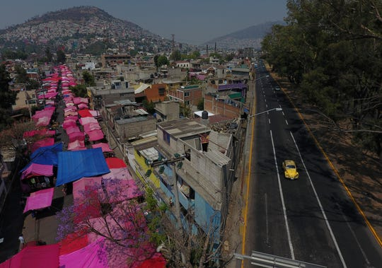 Pink tarps protect street stalls from the sun, as a reduced, but still active, street market takes place alongside a virtually deserted highway, in Mexico City, Sunday, March 29, 2020.