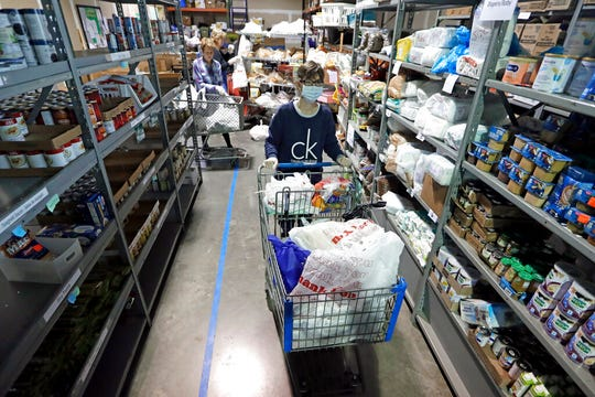 In this April 9, 2020, photo, worker Laura Burbank pushes a cart filled with food for a family through the pantry at GraceWorks Ministries food pantry in Franklin, Tenn.