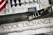 This July 16, 2013 file photo shows a street sign for Wall Street outside the New York Stock Exchange in New York.