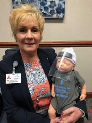 Deaconess Women's Hospital CEO Christina Ryan holds a lifelike baby doll wearing a plastic face shield. The shields are being manufactured by Berry Plastics.