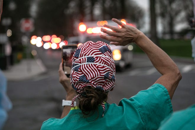 VALHALLA, NEW YORK - APRIL 14: (EDITORIAL USE ONLY) Hospital ER/RN Adele Rushneck-Feeney waves outside the Westchester Medical Center as first responders pass by in a caravan of sirens and lights on April 14, 2020 in Valhalla, New York. The first responders arrived in EMS ambulances, fire department trucks and police vehicles to give thanks to healthcare workers for their efforts in combating the coronavirus (COVID-19) pandemic in Westchester County, NY. (Photo by John Moore/Getty Images)