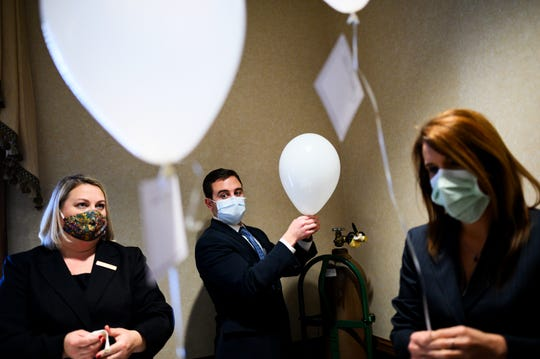 From left, Samantha Kennedy, Jay McAfree and Tiffany Holtzclaw demonstrate how they create message card balloons that are placed inside the chapel in place of family members for funeral services during the coronavirus pandemic at Thomas McAfee Funeral Home Northwest Chapel Thursday, April 16, 2020.