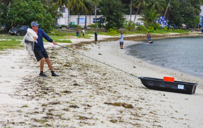Mangilao resident Freddie Guerrero hauls his drag boat containing his gear and bounty ashore after spending part of his morning, with other talayerus catching mañahak, or juvenile rabbit fish, in the waters of East Hagåtña Bay in this April 16 file photo.