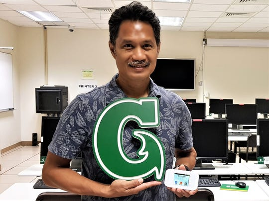 Manny Hechanova of the University of Guam accepts a donation of 30 mobile hotspot devices and 4G LTE data from IT&E.