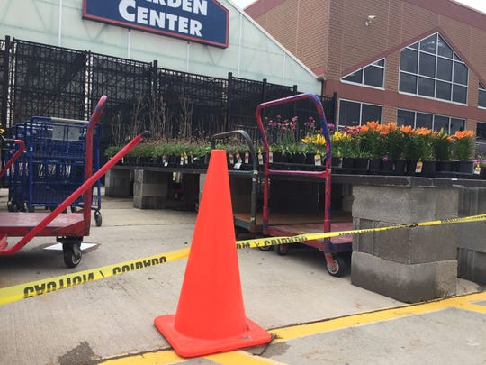 Orange cones and caution tape block customers at the Lowe's store in Genoa Township from shopping in the store's garden center, Monday, April 14, 2020. The section of the store is closed due to state restrictions in place to combat COVID-19 spread.
