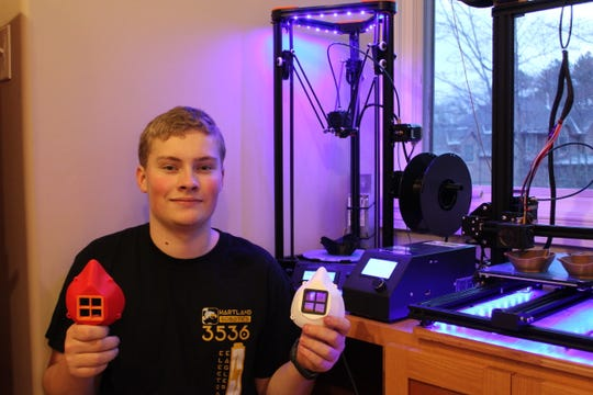 Aidan Cellarius, a sophomore on the Hartland High School robotics team, shows two of the personal protection masks he produced on a 3D printer to help prevent exposure to COVID-19 for front line medical staff.