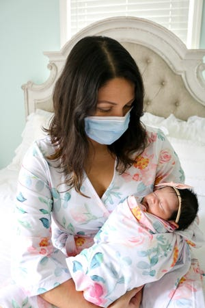 Debora Garcia and her newborn daughter, Elena Grace. Garcia gave birth to Elena at Baptist Health Louisville April 6 while still recovering from COVID-19. She had to wear a mask throughout the labor and delivery, and while she breastfeeds.