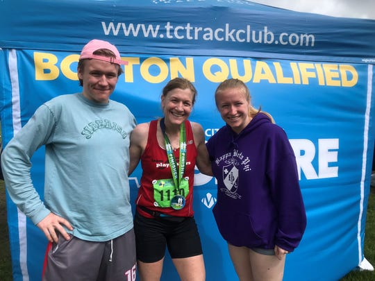 Laurie Mooney, Laurie Mooney, middle, is pictured with both her kids after finishing the Traverse City Bayshore Marathon to qualify for Boston.
