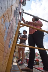 Robin Shoup and Ruthie Akuchie paint a mural on the side of Fork & Fingers in a file photo.