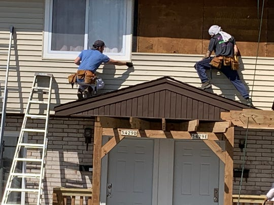 Workers from Berrada Properties install siding at an apartment building on North 92 Street near Timmerman Airport last month.