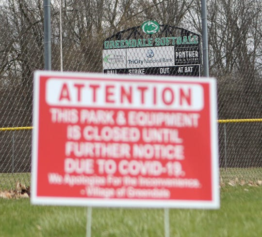 A sign in front of the Greendale softball field announces the park is closed due to coronavirus.