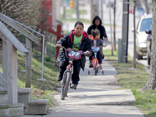 Marlon Johnson, 10, rides his bike down East Locust Street in Milwaukee as his mother, Marquida Brown, and his brother, Damien Essex, 4, are riding behind on Thursday, April 16, 2020. Wisconsin schools will be closed for the rest of the school year and many businesses will stay shuttered until the end of May under action Gov. Tony Evers took Thursday to extend restrictions to contain coronavirus in the state.