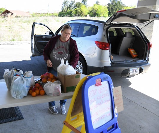 Catherine Bryant begins to load boxes of food items into her vehicle Wednesday at the Mountain Home Food Basket. The Food Basket has closed ts lobby to the public and is offering clients a drive-through pickup line in order to continue to receive food disbursements.