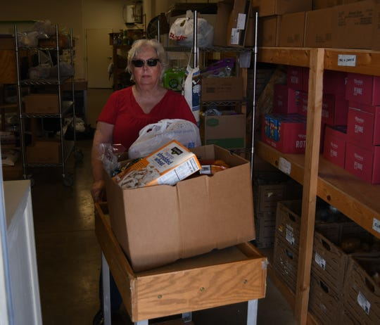 Volunteer Debbye Barreda uses a cart to roll a client's food items out to them Wednesday at the Mountain Home Food Basket. In the Food Basket's drive-through line, volunteers box up a client's food items and leave them on the table, where the client then loads the boxes into their vehicle.