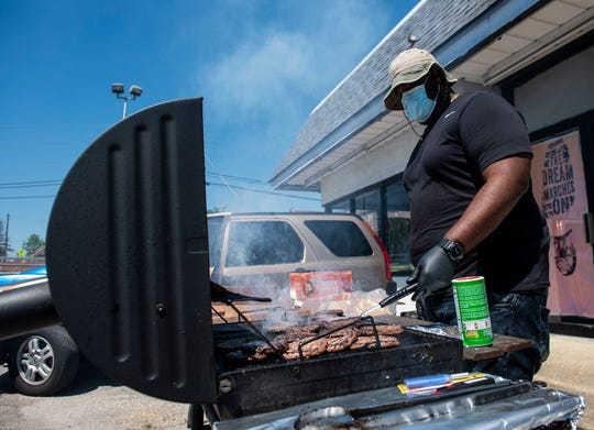 Wil Milner works the grill as Hateless Foundation serves up free hamburgers and hot dogs in Montgomery, Ala., on Thursday, April 16, 2020.