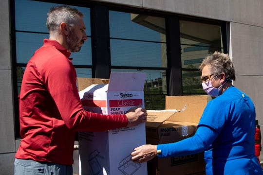 Red Bicycle Coffee owner David Trett delivers food to Marla Jackson for health care workers outside of Saint Thomas Midtown Hospital Thursday, April 16, 2020, in Nashville, Tenn.