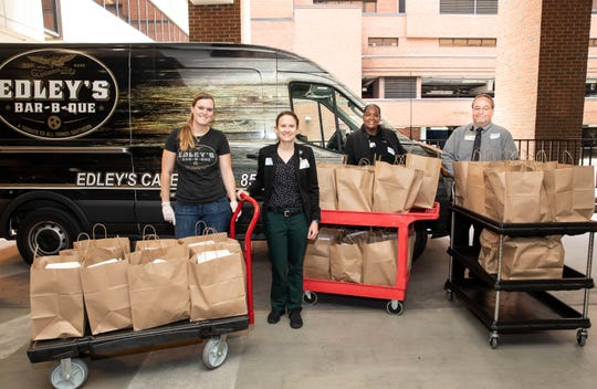 Katie Larson, left, delivers barbecue from Edley's Bar-B-Que in Sylvan Park to Vanderbilt food services executives, left to right, Melissa Newman, Maretta Ligon, and Kevin Houy.  The donation was made through Feed the Front Line Nashville, a nonprofit providing meals to healthcare workers treating COVID-19 patients that was started by Vanderbilt students and recent alumni.
