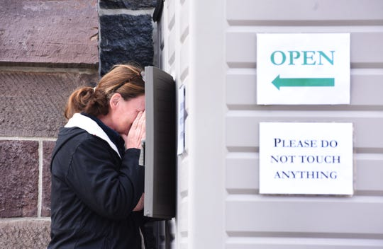 Local Christians make their confession to Rev. Daniel O'Mullane outside new confession booth i front of  the Our Lady of Mount Carmel church where parishioners can come safely.
