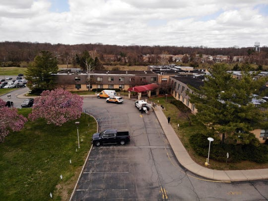 Ambulance crews are parked outside Andover Subacute and Rehabilitation Center in Andover, N.J., on Thursday April 16, 2020.   Police responding to an anonymous tip found more than a dozen bodies Sunday and Monday at the nursing home in northwestern New Jersey, according to news reports.  (AP Photo/Ted Shaffrey)