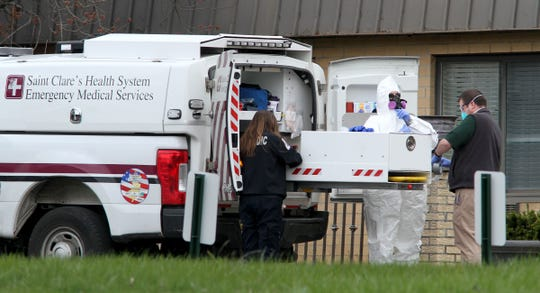 A paramedic dons a hazmat suit outside the Andover Rehabilitation and Subacute Care I and II in Andover Township Thursday, April 16, 2020.  State officials said on Thursday that a total of 35 residents had died at the home, which is made up of two separate buildings, since the end of March, with 19 of of those deaths linked to COVID-19