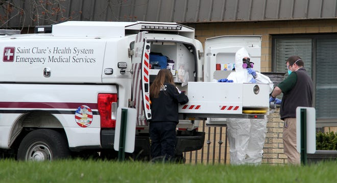A paramedic dons a hazmat suit April 16 before entering the Andover Subacute Rehabilitation Center, in Andover Township, to recover bodies of residents who died of COVID-19. As of May 4, 67 residents have died at Andover's two nursing homes, which have had a history of inspection citations.