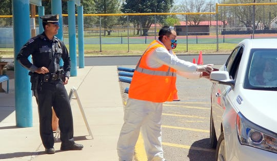 At left, New Mexico State Police officer Munoz kept an eye on traffic control at the Deming Senior Citizen's Center.