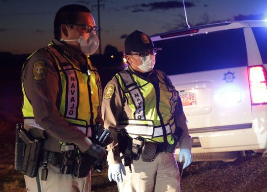Officer Brandon Jim, left, and Officer Darlene Foster wear personal protective equipment on April 1 during a checkpoint by the Navajo Police Department's Shiprock district on U.S. Highway 64 in Hogback.
