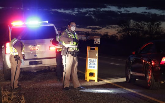 Navajo Police Officer Brandon Jim, center, directs traffic at a checkpoint on April 1 by the department's Shiprock district on U.S. Highway 64 in Hogback.