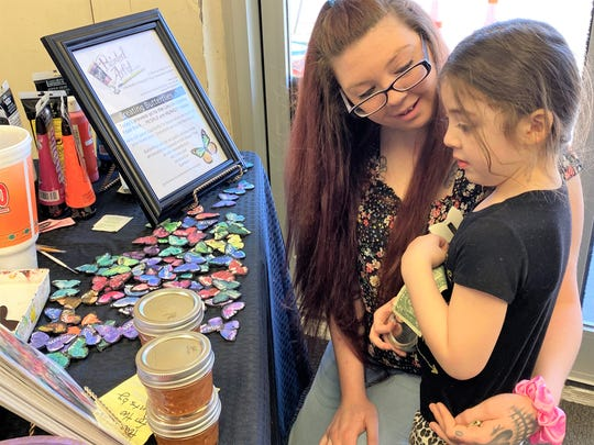 Adelina Gutierrez, 3, and her mother, Robyn, view the butterflies made by Jana Lynch at the food drive for the Lincoln County Food Bank. Adelina's homemade salsa  was donated for the cause.
