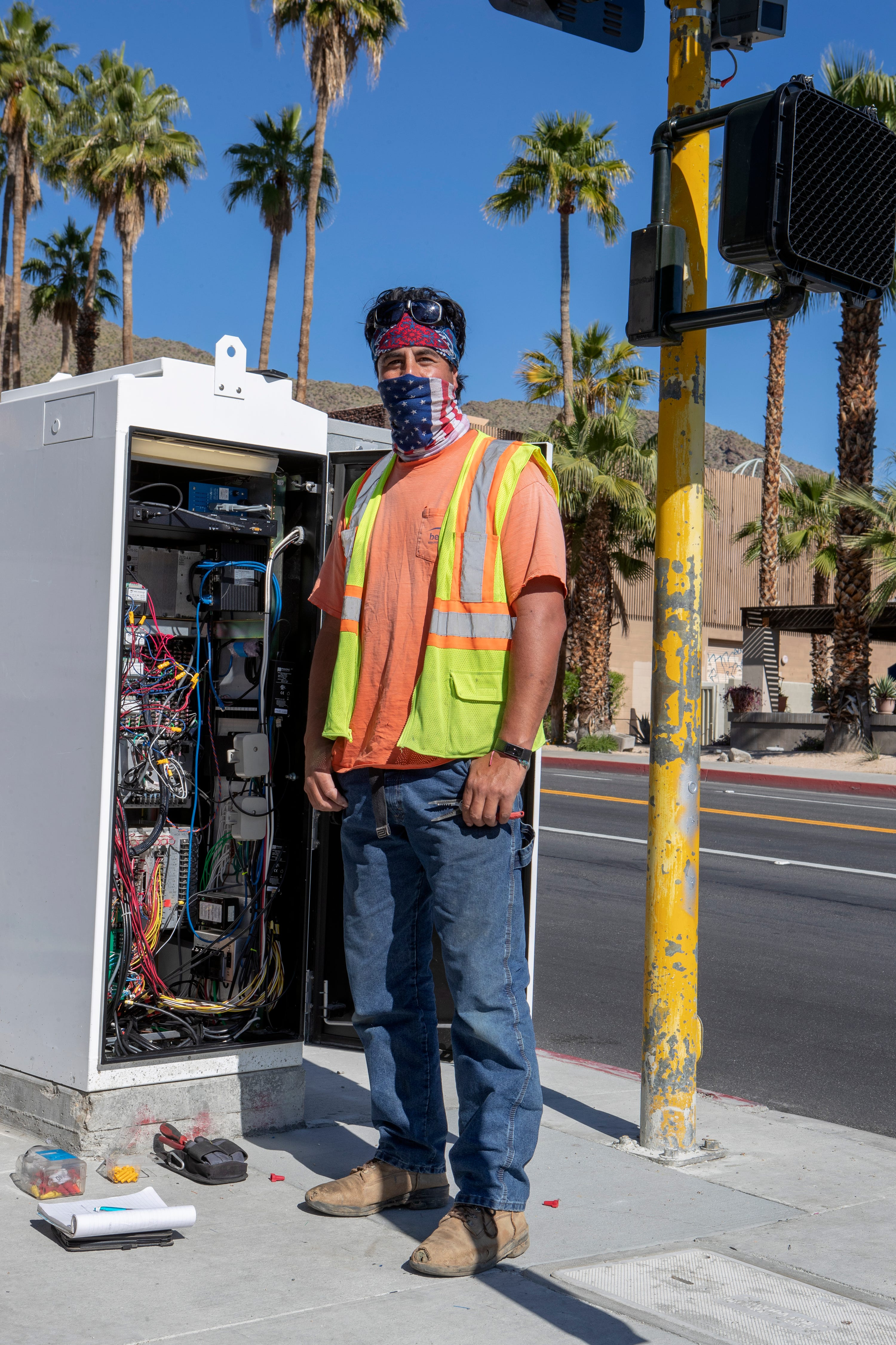 Electrician Steve Estrada works on the traffic signal at Indian Canyon Drive and Ramon Road in Palm Springs, Calif., on Wednesday, April 15, 2020.