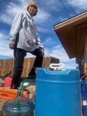 Jamie Lynn Butler fills water bottles at her grandmother's house in Cameron, Ariz. in the Navajo Nation. Butler's home, 2 miles from grandma's place, lacks running water or electricity, as do 7,500 other homes in the nation.