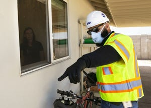Pablo Barajas, a Cox Communications field technical specialist, communicates with Alex Palmer through a window while installing internet at their residence in Phoenix on April 15, 2020.