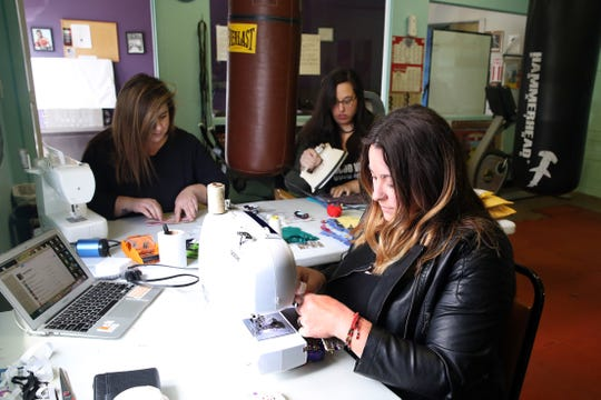 From right, Jamie Palamino, along with her friends Sara Pagan and Prisilla Acosta, work on sewing surgical masks for healthcare workers at Floyd Patterson Boxing Club in Highland April 15, 2020.