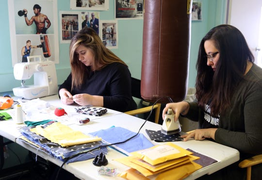 Sara Pagen and Prisilla Acosta, work on sewing surgical masks for healthcare workers at Floyd Patterson Boxing Club in Highland April 15, 2020.